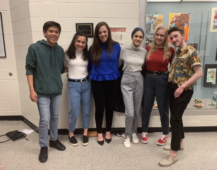 Mrs. Freeman is joined by seniors at their last Art Show.