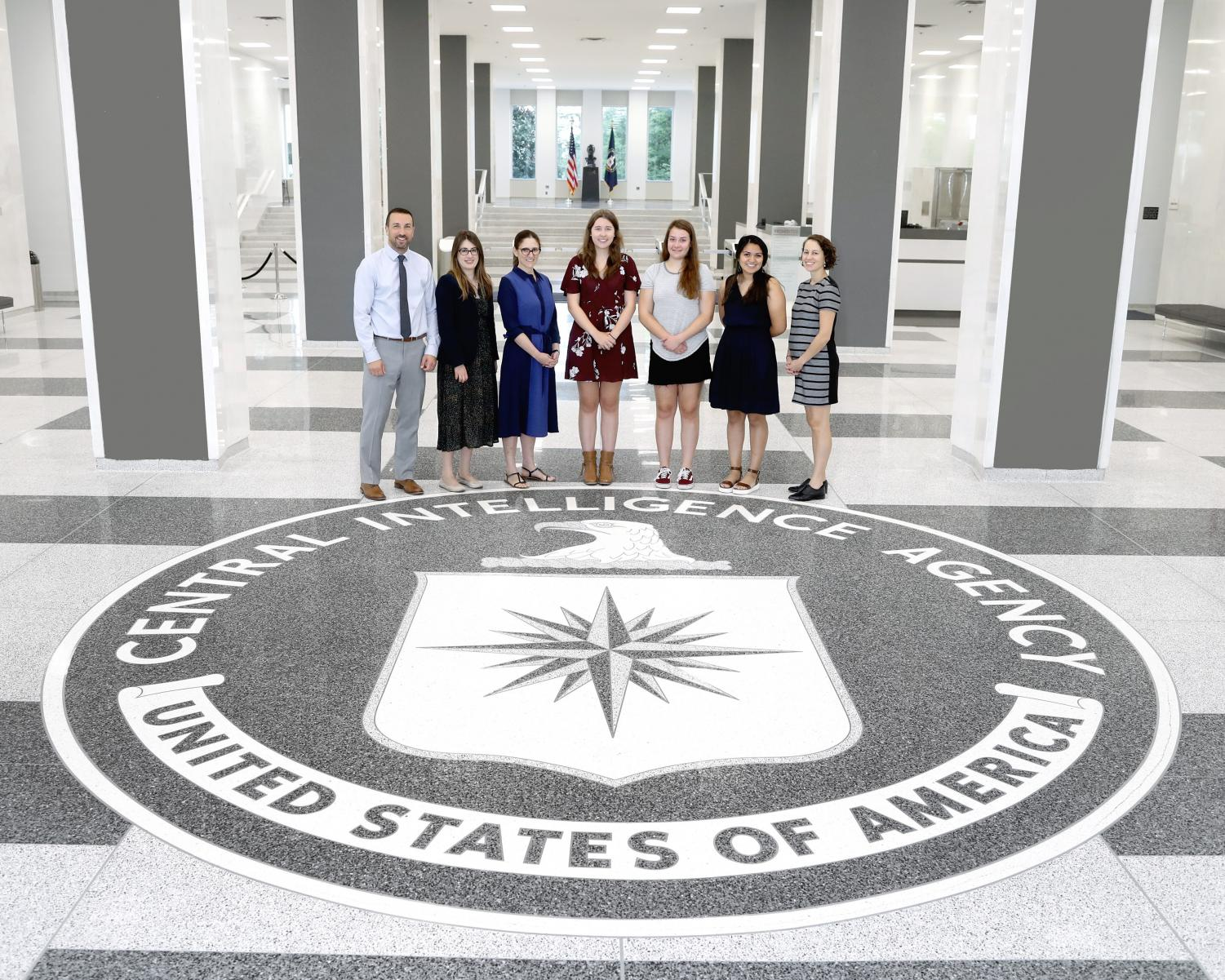 Journalism teacher Mitch Schwartz, Ali Rogan of PBS NewsHour, Leah Clapman of PBS NewsHour, Morgan Fischer, Alison Pataky, Karen Ramos and Briget Gansky of PBS NewsHour stand in the entrance of the Old Headquarters Building of the CIA prior to the ceremony.