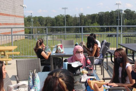 Enjoying being outside together on a beautiful day, seniors enjoy the time together as they eat their lunch.