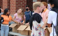 Handing out t-shirts on the first day of school, SCA President Simren John hopes the return to school brings a renewed sense of school spirit.